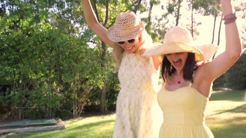 Two women wearing sunglasses and straw hats dance  Footage