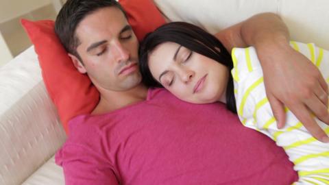 Steadicam shot tracks along sleepy couple relaxing Footage