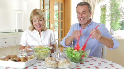 Senior Couple Seated Around Dining Table Serving O stock footage