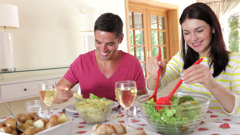 Couple Seated Around Dining Table Serving One Anot stock footage