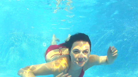 Underwater view as woman swims towards camera and  Footage