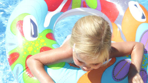 Girl in inflatable rubber ring paddles towards cam Footage