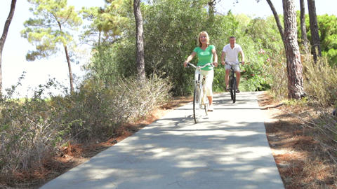 Long shot of romantic senior couple cycling along Live Action