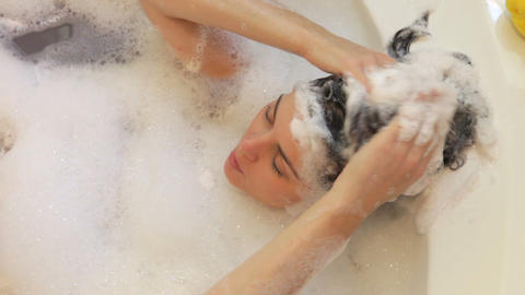 Relaxed woman lying in bubble filled bath washing  Footage