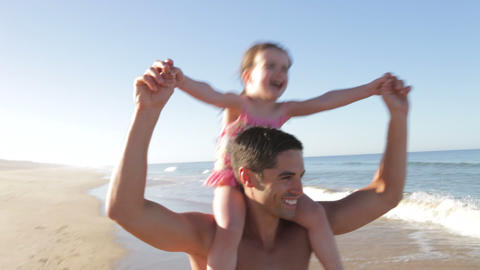 Father Running Along Beach Carrying Daughter On Sh Footage