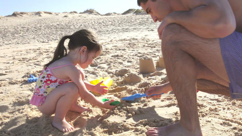Father Helping Daughter To Build Sandcastle On Bea Footage