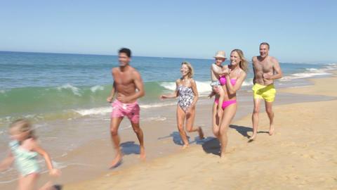 Multi Generation Family Running Along Beach Footage