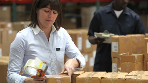 Factory Worker Sealing Packages With Tape stock footage