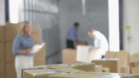 Shallow Focus Of Workers Taking Boxes From Belt stock footage
