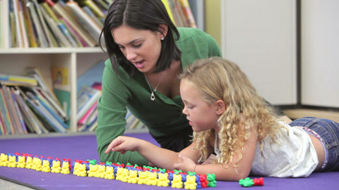 Teacher Showing Girl How To Count With Plastic Toy stock footage