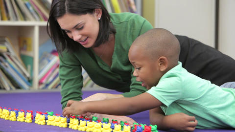 Teacher Showing Boy How To Count With Plastic Toys stock footage