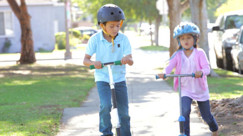 Two Children Riding Scooters Towards Camera Footage