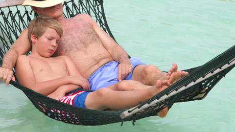 Grandfather And Grandson Relaxing In Beach Hammock Footage