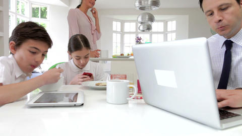 Family Using Digital Devices At Breakfast Table Footage