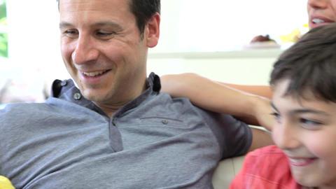 Hispanic Family Sitting On Sofa Talking Together Footage