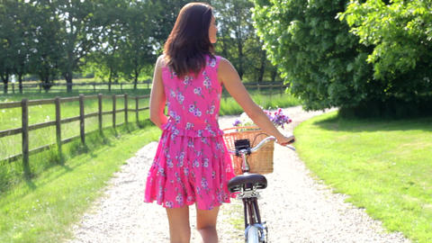 Attractive Woman Pushing Cycle Along Country Lane Footage