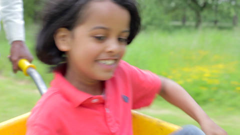 Young Boy Being Given Ride In Wheelbarrow By Fathe Footage
