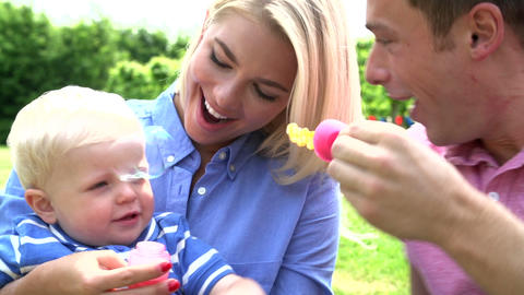 Parents Blowing Bubbles For Young Boy In Garden Footage