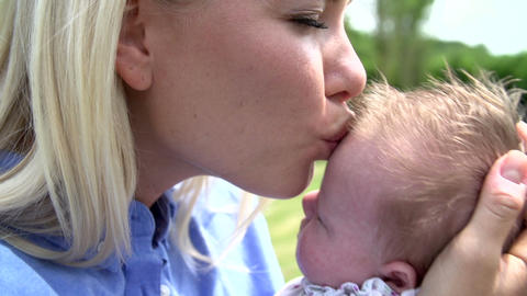 Mother Kissing Baby Daughter In Garden Footage