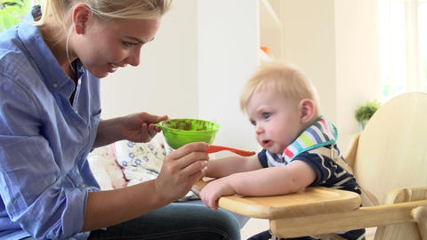 Mother Feeding Baby Boy In High Chair stock footage