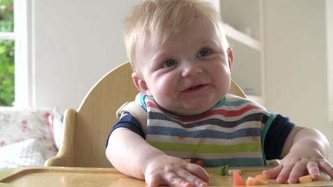 Baby Boy Eating Fruit In In High Chair Footage