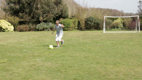 Young Boy Playing Football In Garden stock footage