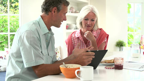 Middle Aged Couple Looking At Digital Tablet Over Footage