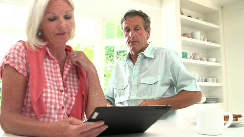 Middle Aged Couple Looking At Digital Tablet Havin Footage