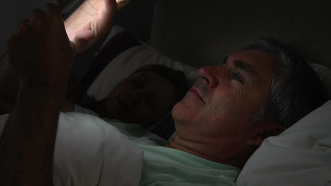 Middle Aged Couple In Bed With Man Using Tablet Co Footage