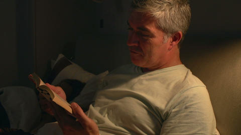 Middle Aged Couple In Bed With Man Reading Book Footage