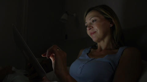Middle Aged Couple In Bed With Woman Using Tablet Footage