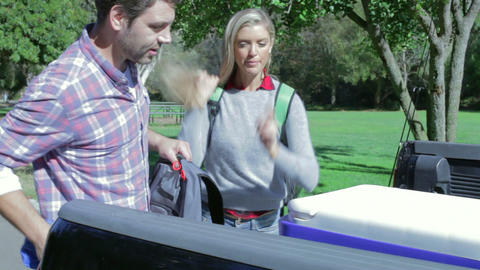Couple Unpacking Pick Up Truck On Camping Holiday Footage