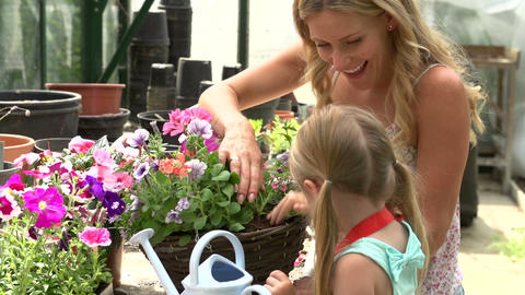Mother And Daughter Watering Plants In Greenhouse Footage