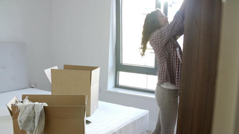 Woman Moving Into New Home Unpacking Clothes In Be Footage