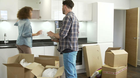 Couple Moving Into New Home And Unpacking Boxes Footage