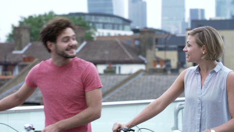 Couple Pushing Bikes With City Skyline In Backgrou Footage