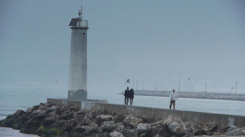 Couple walking on cloudy coast Stock Video Footage