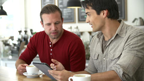 Two Male Friends In Coffee Shop Looking At Digital Footage