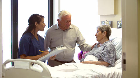 Nurse Talking To Senior Couple In Hospital Room Footage