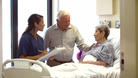 Nurse Talking To Senior Couple In Hospital Room Footage