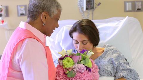 Volunteer Brings Bunch Of Flowers To Female Patien stock footage
