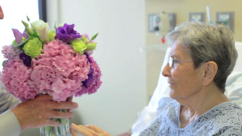 Senior Man Visits Wife In Hospital Room With Flowe stock footage