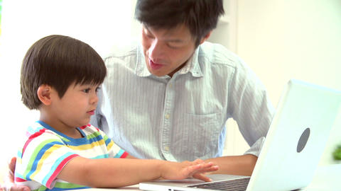Asian Father Helping Son To Use Laptop At Home Footage