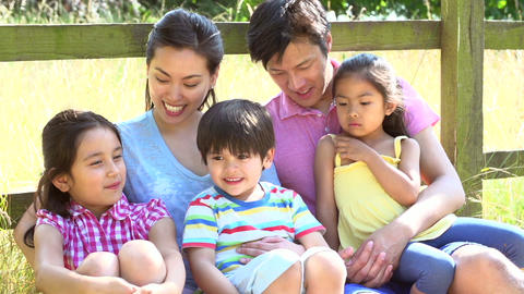 Asian Family Relaxing By Fence On Walk In Countrys Footage