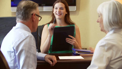 Older Couple Talking To Financial Advisor In Offic stock footage