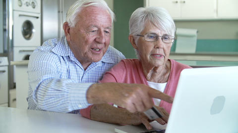 Senior Couple Booking Vacation Online Using Digita Footage