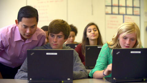 Teacher Helping High School Students Using Laptops Footage