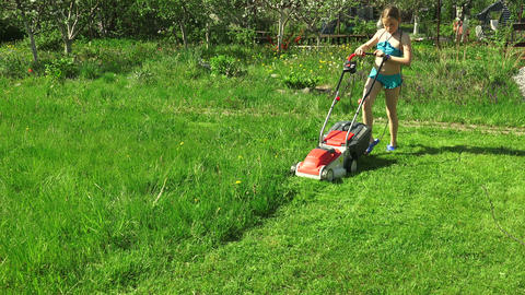 The girl child mowing the lawns. 4K Footage