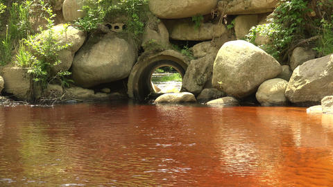 The river flows through a pipe. 4K Footage