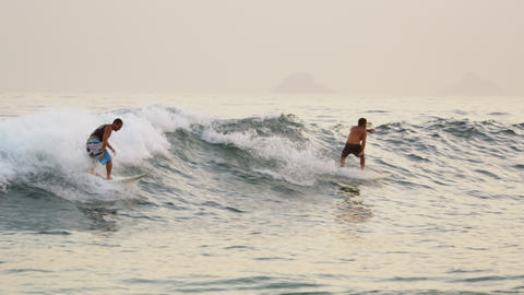 Close shot of bodyboarders and surfers offshore from Rio de Janeiro's coast Footage
